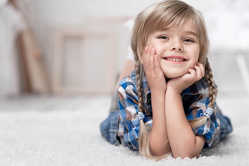 Image of a small girl laying on carpet with no chemicals due to green carpet cleaning Alpine