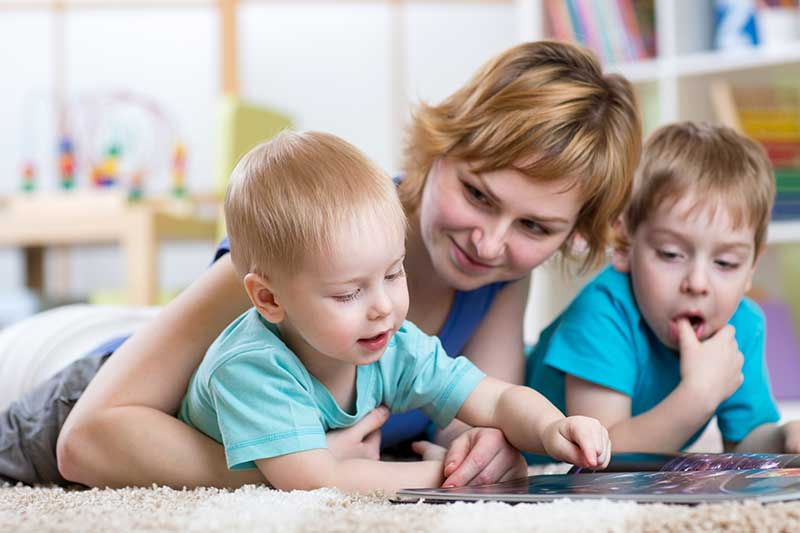 Image of a mother and children reading on the carpet after taking advantage of fast carpet cleaning in West Valley City
