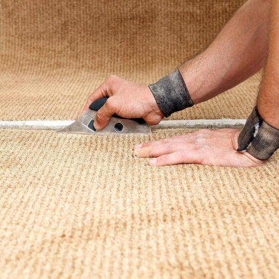 An installer is using cushion back cutter to trim carpet for seaming. The worker is wearing wrist bands to ease Carpal Tunnel discomfort and prevent tendonitis. The hands are callused on the knuckles from repetitive handling and fist-to-carpet contact.