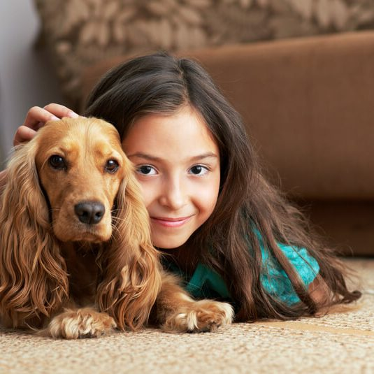 The girl is lying on floor with dog